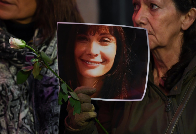 A woman holds a photo of late French actress Marie Trintignant, as women from feminist organizations demonstrate on Mar. 12, 2018 in front of the Rockstore venue, against a concert of French singer Bertrand Cantat as it takes place in Montpellier, southern France. Cantat told AFP on March 12, 2018, he was renouncing to perform in summer festivals as he was facing mounting opposition to his concerts, 15 years after his actress girlfriend Marie Trintignant died at his hand.