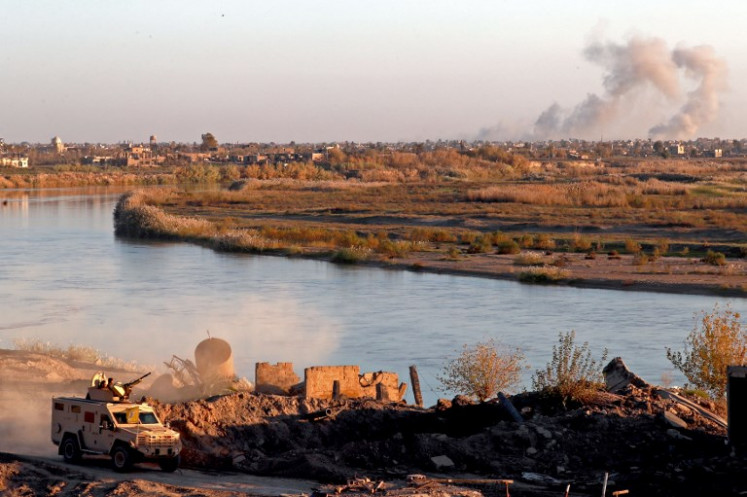 Smoke billows after bombings in the Deir Ezzor province as a vehicle of the Syrian Democratic Forces (SDF) stops in Hajin, in the Deir Ezzor province, eastern Syria, on Dec. 15. Kurdish-led forces seized the Islamic State's main hub of Hajin on Dec. 14, a milestone in a massive and costly US-backed operation to eradicate the jihadists from eastern Syria. The Syrian Democratic Forces secured Hajin, the largest settlement in what is the last pocket of territory controlled by IS, the Syrian Observatory for Human Rights said.