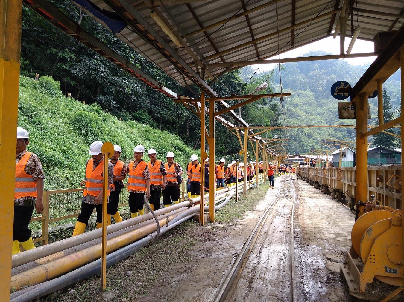 Visitors walk past a mining area.