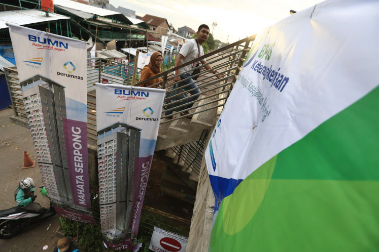 Passengers walk near banners advertising a TOD housing project at Rawa Buntu Station in South Tangerang on Dec. 16.