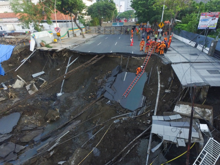 Firefighters check the condition of the soil inside the sinkhole on Jl. Raya Gubeng in Surabaya in East Java on Dec. 19.