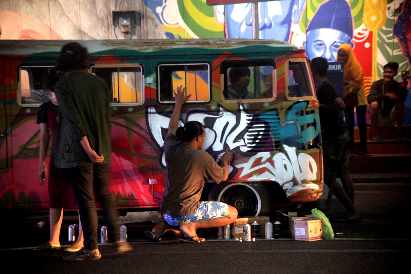 Spray time: Mural artists decorate a vintage car. JP/Maksum Nur Fauzan