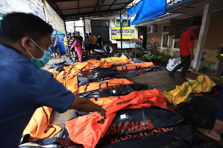 An SAR personnel tends to the recovered bodies of tsunami victims at Puskesmas Carita (community health center) on Sunday in Pandeglang regency, Banten.