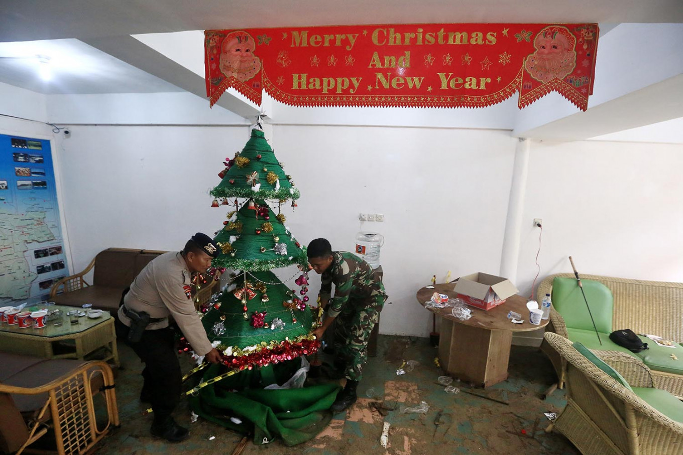 Sad Christmas: A police officer and a member of the military remove a Christmas tree from a tsunami-damaged building in the Carita Beach area, Pandeglang, Banten, on Monday, December 24, 2018. JP/Dhoni Setiawan