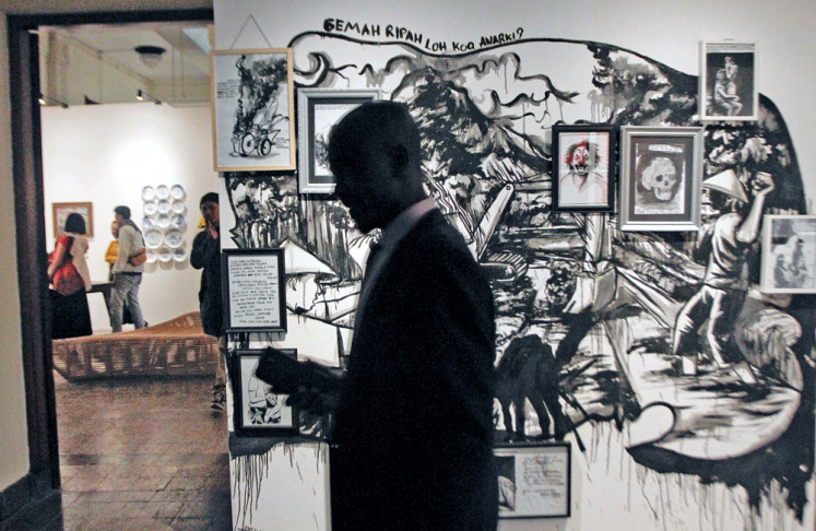 """Art statement: A visitor walks in front of Mufti """"Amenk"""" Priyanka's work during the """"Art_Unltd: XYZ"""" exhibition in Bandung, West Java."""