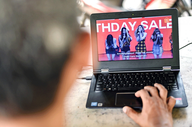Korean fever: A man watches a commercial featuring K-pop supergroup Blackpink on his laptop in Jakarta on Dec. 12, 2018.