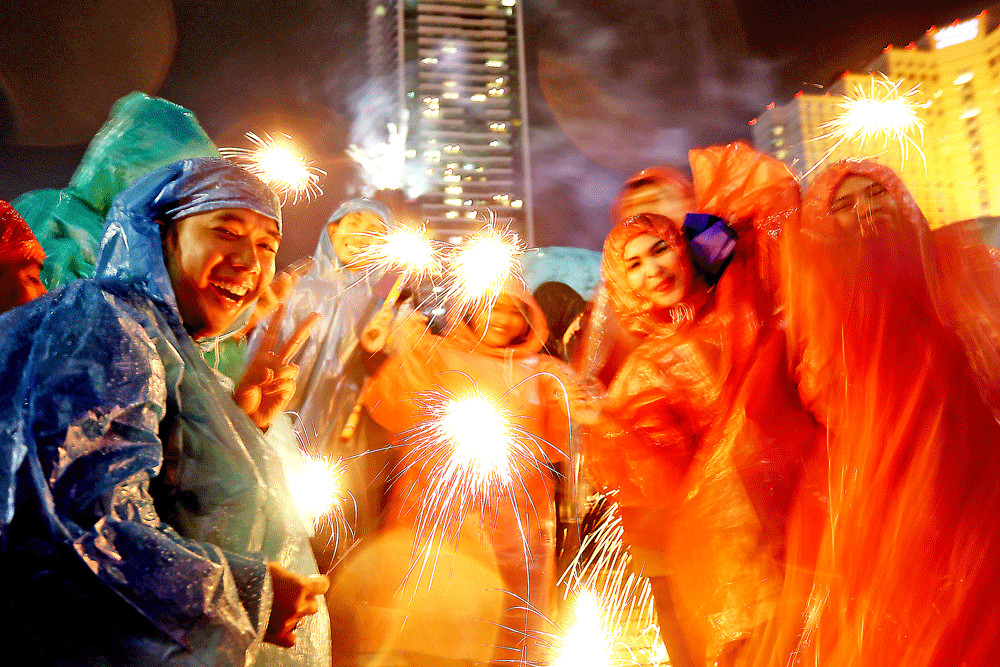 Full of cheer: Jakartans celebrate New Year's Eve with fireworks at the Hotel Indonesia traffic circle on Monday. Rain that had been pouring since the afternoon did not stop revelers from welcoming 2019 with joy.
