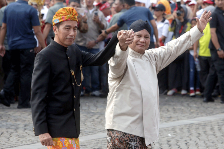 """Clean campaign: President Joko """"Jokowi"""" Widodo (left) and his challenger in this year's presidential election, Prabowo Subianto, walk hand-in-hand during an event held in Jakarta on Sept. 23, 2018, in which they vowed to combat hoaxes and ethnic, religious, racial and ideological sentiments during the campaign period."""