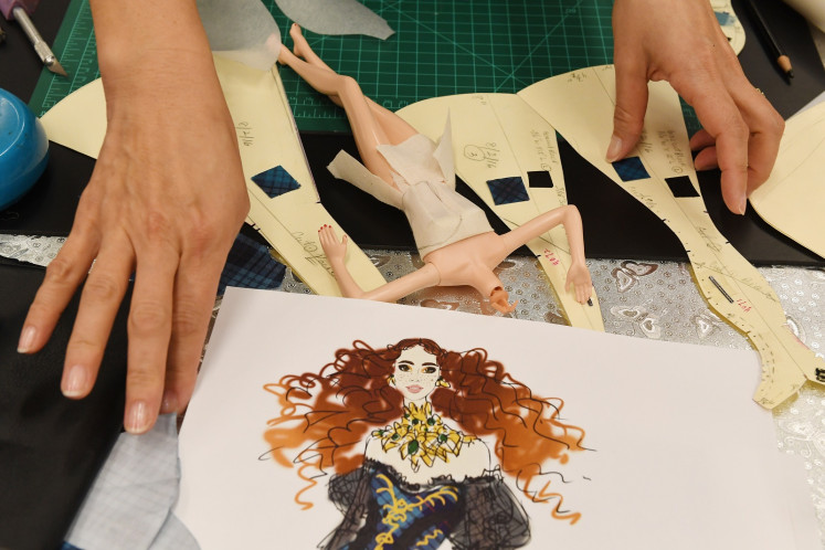 Stylist Carlyle Nuera works on fashion for Barbie doll prototypes at a workshop in the Mattel design center as the iconic doll turns 60, in El Segundo, on December 7, 2018.
