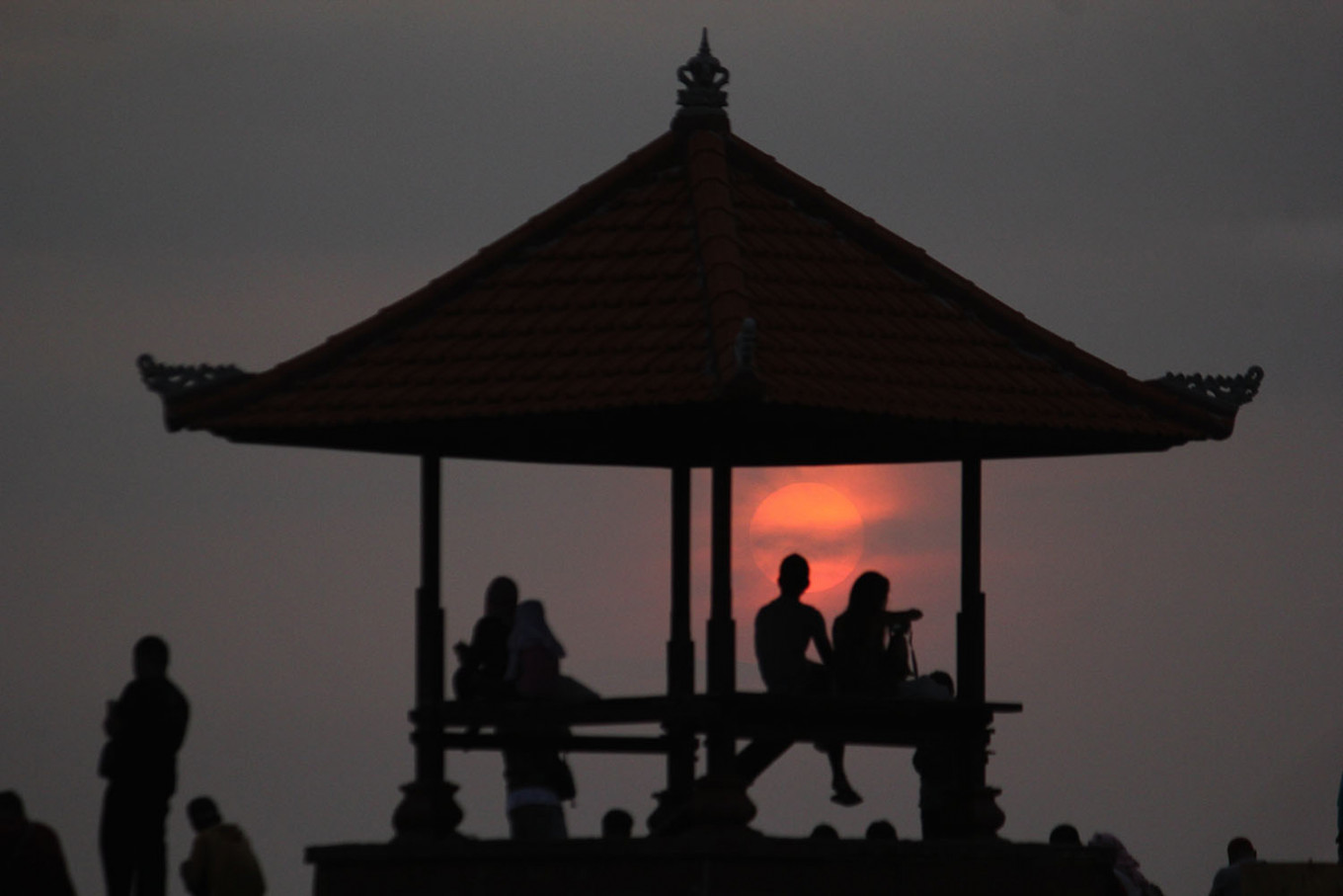 New dawn: Tourists watch the sunrise at Sanur Beach in Bali on Tuesday. JP/Zul Trio Anggono