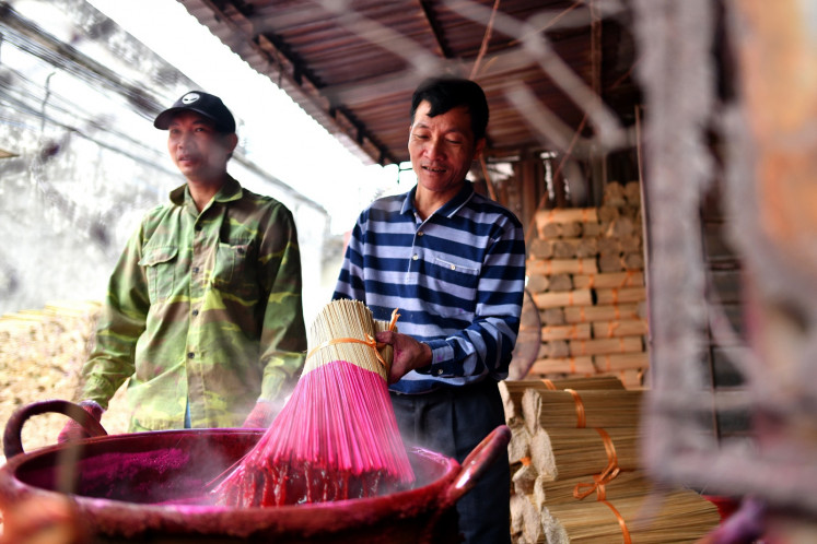 This picture taken on January 4, 2019 shows Vietnamese workers dying bamboo incense sticks at a workshop in the village of Quang Phu Cau on the outskirts of Hanoi.