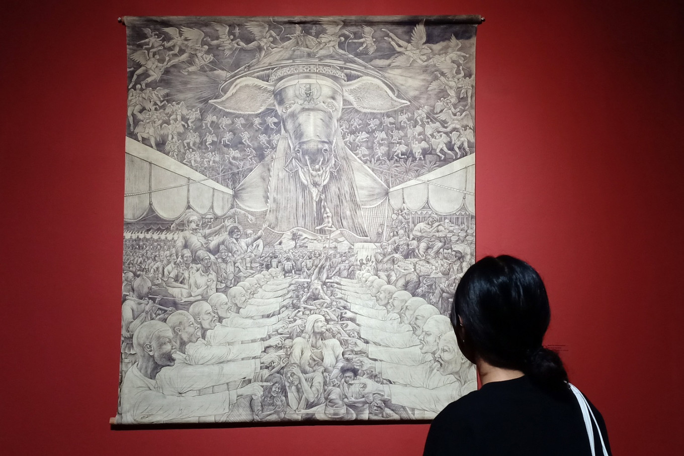 A visitor admires a drawing by Aris Prabawa during the 'Hadap Hidup' exhibition.