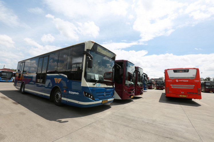 An older model Transjakarta bus parks among newer ones at the depot in Cawang, East Jakarta, on Jan. 2. For better or worse, the busway has changed the way Jakartans see buses.