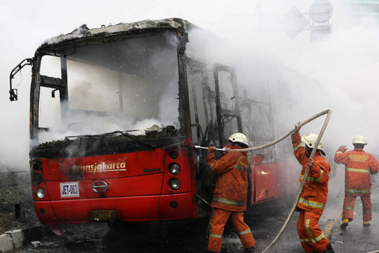 Firefighters extinguish a fire on a Transjakarta bus at the Hotel Indonesia traffic circle in 2012. Just like any new system, the Transjakarta is not without its faults.