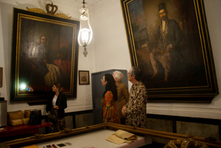 Art restorer Michaela Anselmini (left), Italian Ambassador to Indonesia Vittorio Sandalli (right) and a representative from the palace's cultural section, Gusti Kanjeng Ratu Bendara (second left), look at paintings in Yogyakarta on Monday. The restoration of paintings is to be finished in late February.