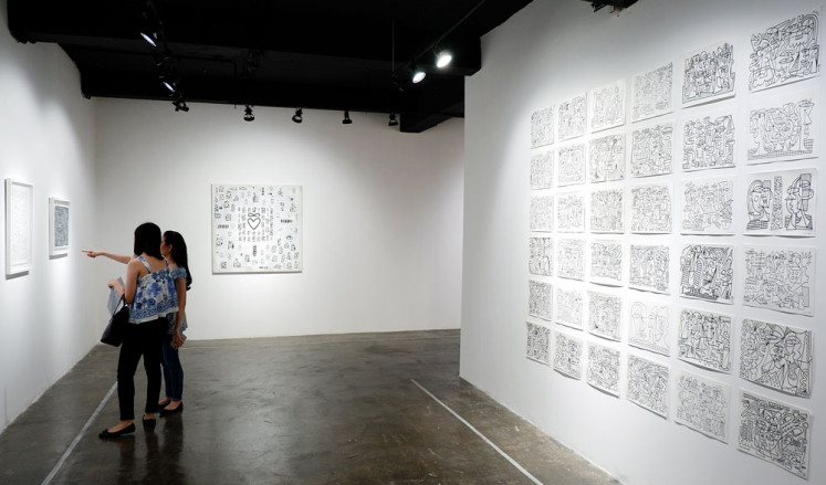 Contrasts and similarities: Two visitors view Abenk Alter's works in his first solo exhibition, at RUCI Art Space in South Jakarta.