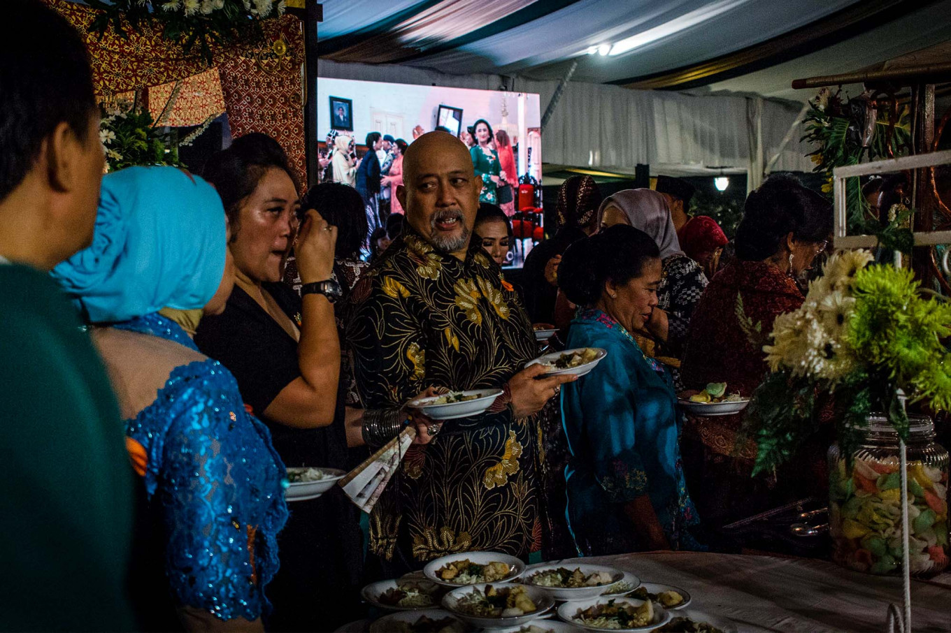 Famous comedian Indro Warkop (center) waits in line with other guests to grab something to eat. JP/Anggertimur Lanang Tinarbuko