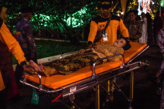 A guest lies on a stretcher as she waits for medical help after fainting while standing in line. JP/Anggertimur Lanang Tinarbuko