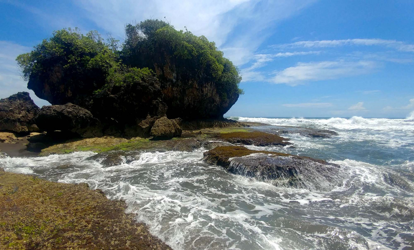 A giant rock is an attraction at Legok Jawa Beach. Due to strong waves and currents, tourists are not allowed to swim there. JP/Arya Dipa
