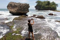 A tourist captures a moment at Madasari Beach. JP/Arya Dipa