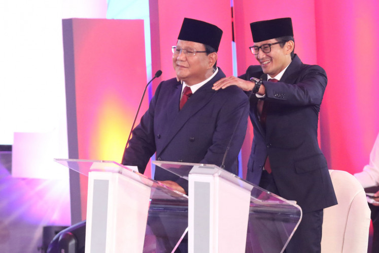 Vice presidential candidate Sandiaga Uno gives his running mate Prabowo Subianto a backrub during the first candidate debate on Jan. 17.