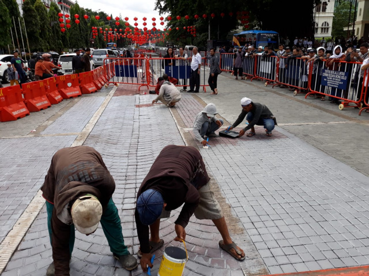 Workers paint over a road mosaic in front of the Surakarta City Hall in Central Java after Muslims groups complained that the street art resembled a Christian cross.