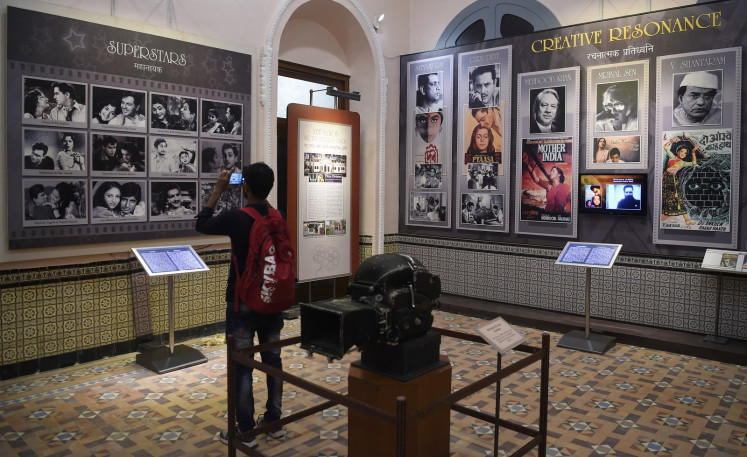 In this picture taken on January 22, 2019, a student takes a picture of a display with images of former Indian movie actors at the National Museum of Indian Cinema (NMIC), the country's first museum showcasing the history of its film industry, in Mumbai.
