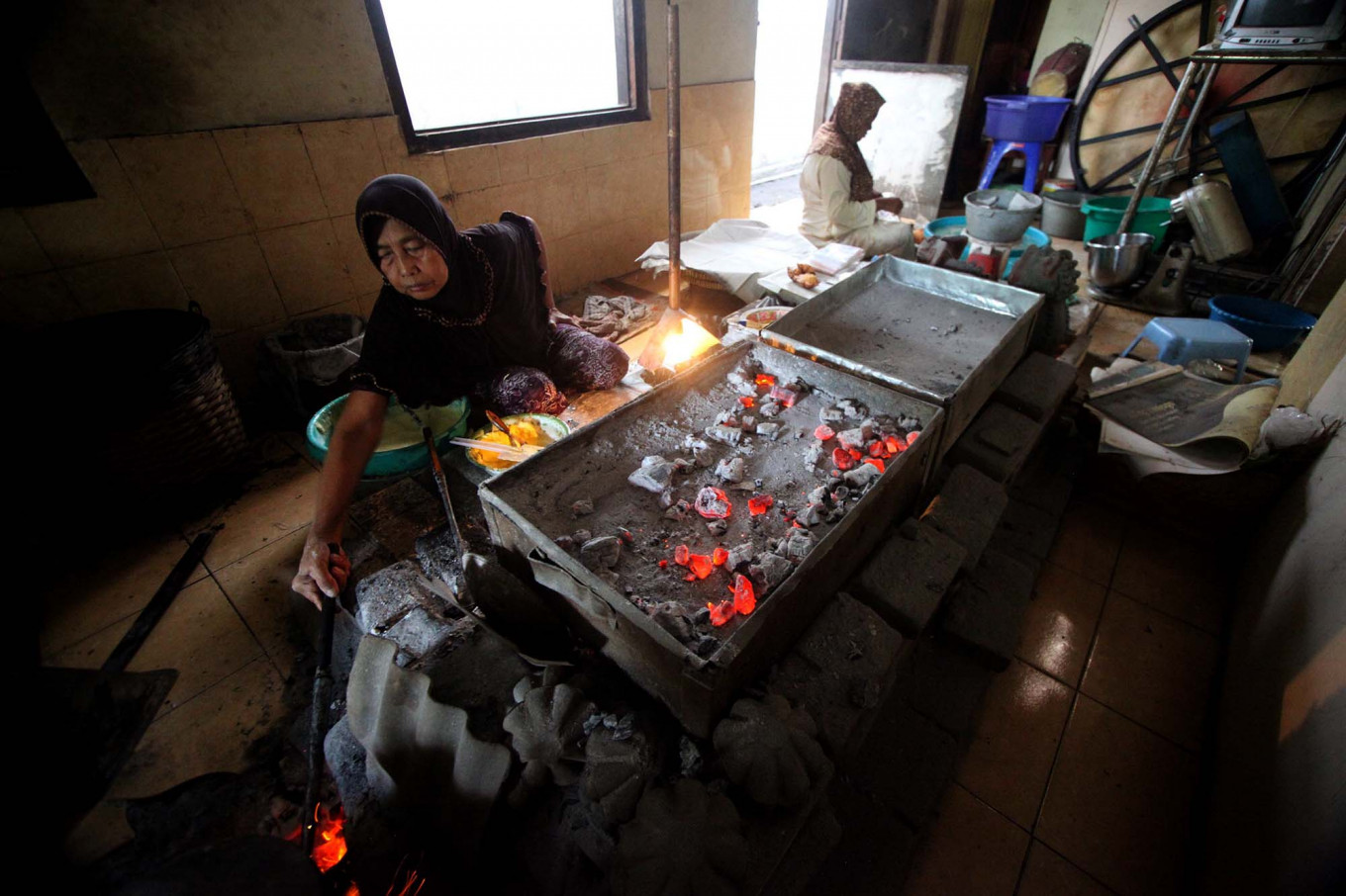 Basiran's wife manages the heat of the oven and the furnace. JP/Boy T. Harjanto
