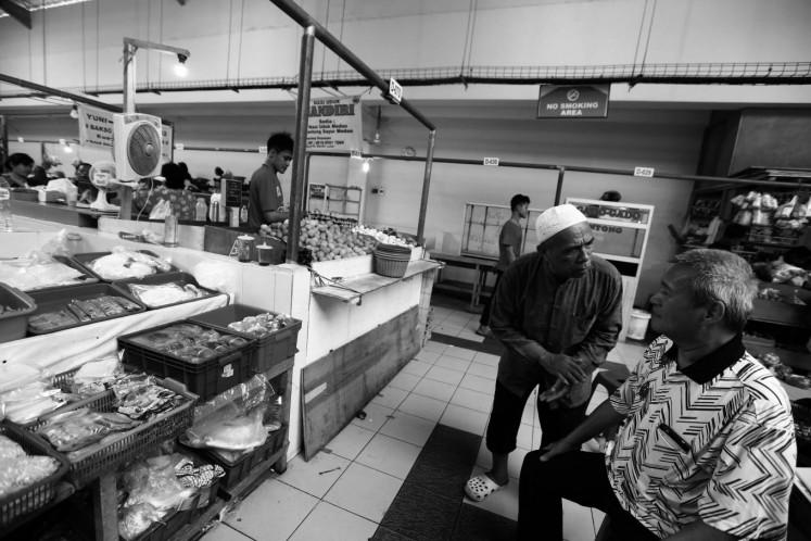 Bambang Winardi talks with another seller at the market.