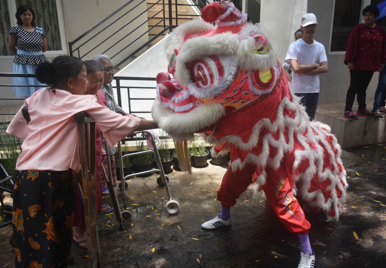 Senior citizens hand 'angpao' (envelopes containing cash) to a 'barongsai' dancer.