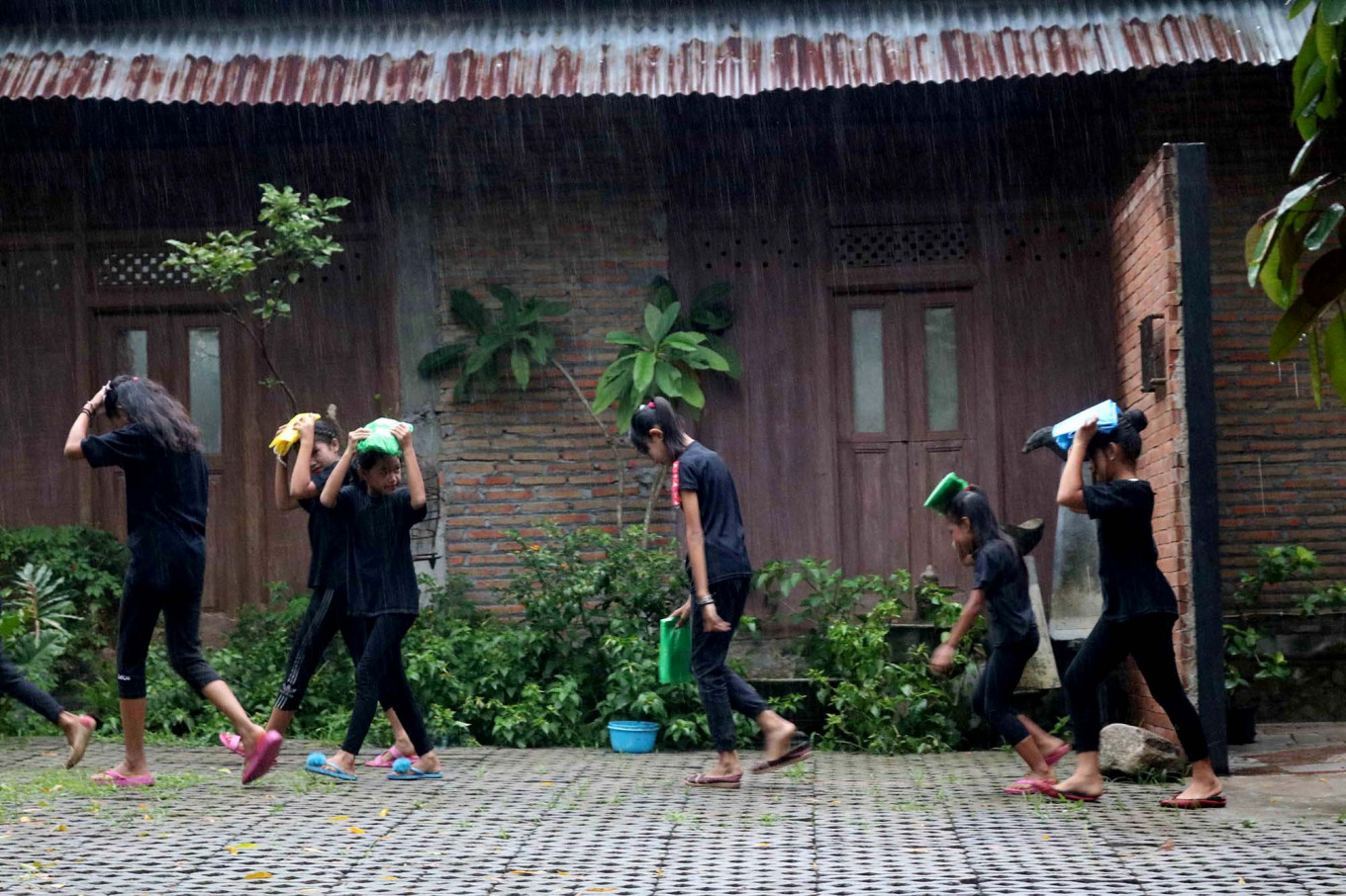 Children walk in the rain before joining the festival. JP/Maksum Nur Fauzan