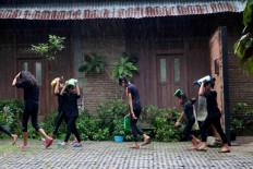 Children walk in the rain before joining the festival. JP/Maksum Nur Fauzan