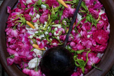 A jug of water filled with rose petals and jasmine acts as a prop for a performance. JP/Maksum Nur Fauzan