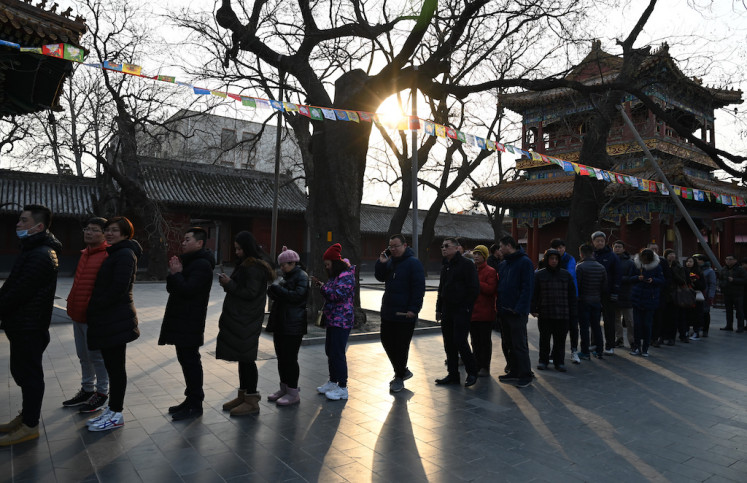 People line up to pray for good fortune at the Yonghegong, or Lama Temple in Beijing on the first day of the Lunar New Year on Feb. 5, 2019. Chinese communities around the world welcomed the Year of the Pig on February 5, ushering in the Lunar New Year with prayers, family feasts and shopping sprees