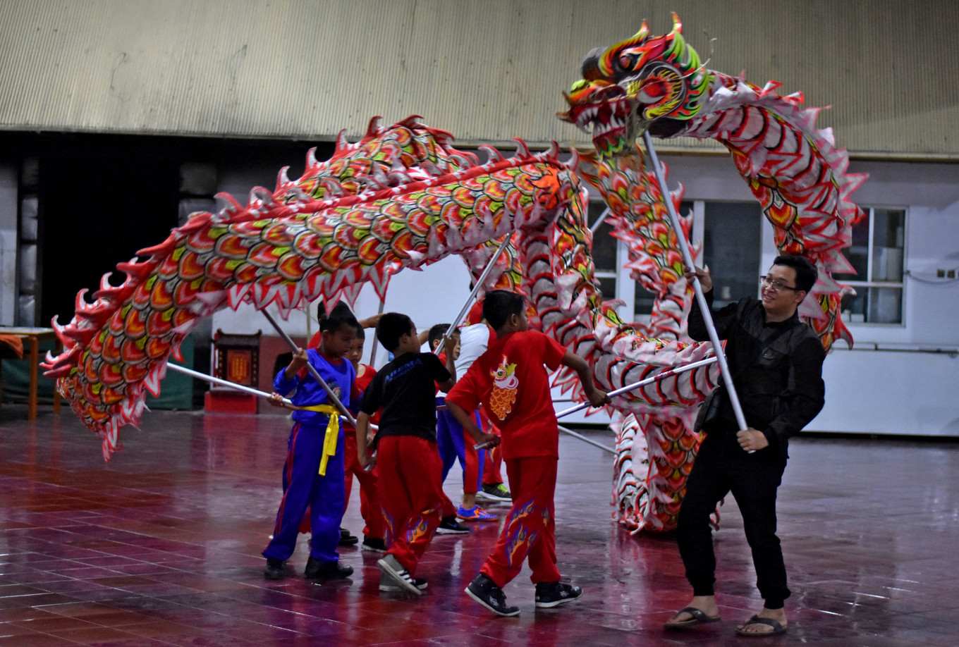Handoko Prayogo (in black suit) trains children in the basic moves of the barongsai (lion dance) and the Leang Leong dragon dance at the Eng An Kiong Chinese temple in Malang, East Java, on Jan. 19. JP/Aman Rochman