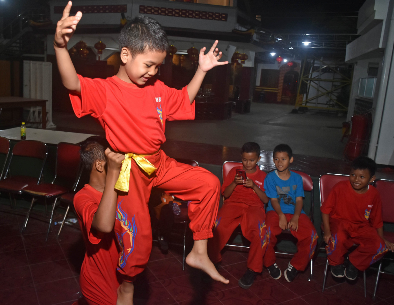 A boy is lifted during a barongsai training session. JP/Aman Rochman
