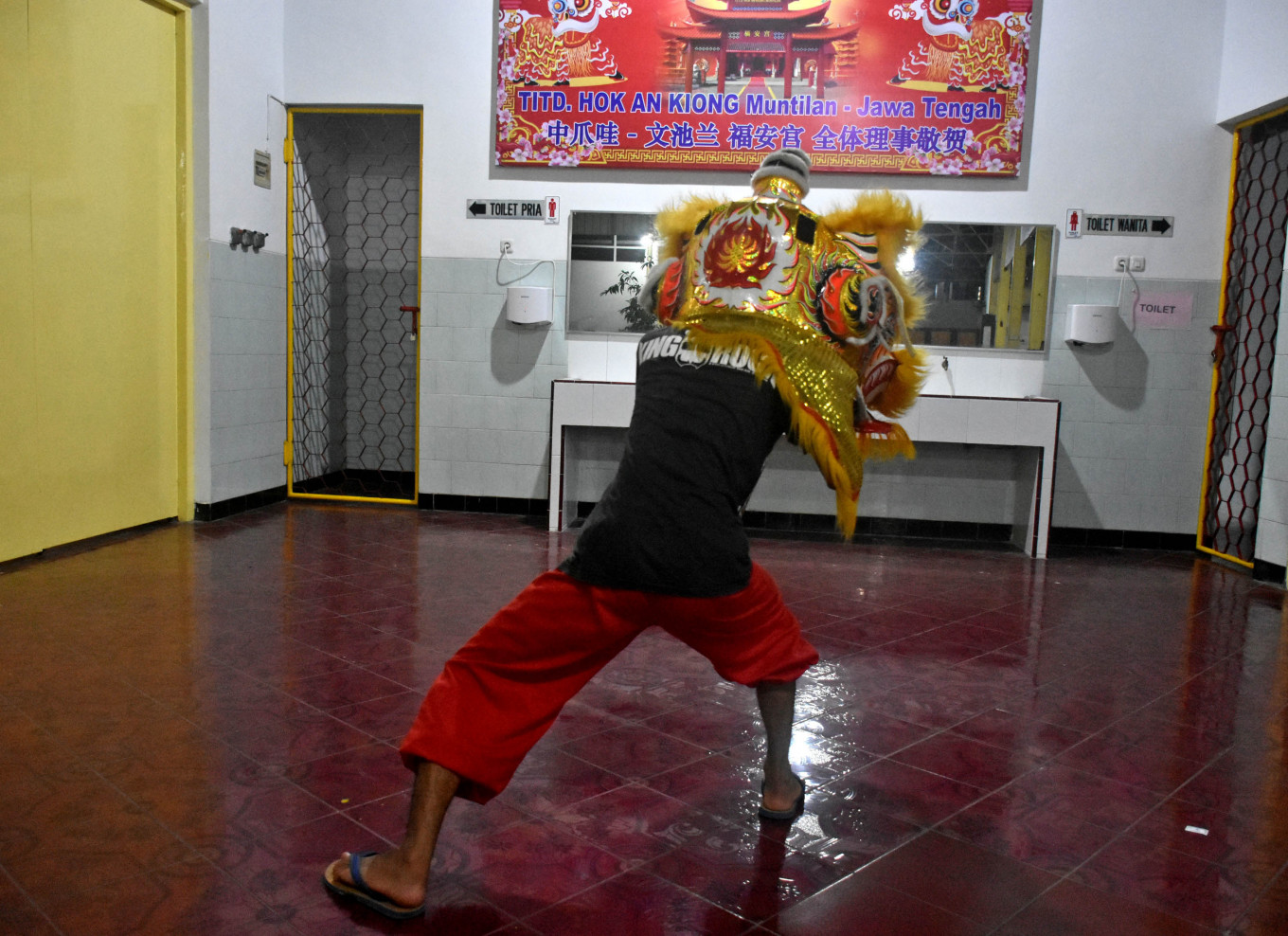 A young man practices in front of the mirror to coordinate the moves of the eyes and ears of the lion mask. JP/Aman Rochman