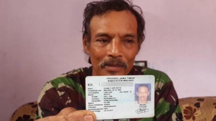 Slamet Hari Natal, a resident of Malang regency, shows his ID card.