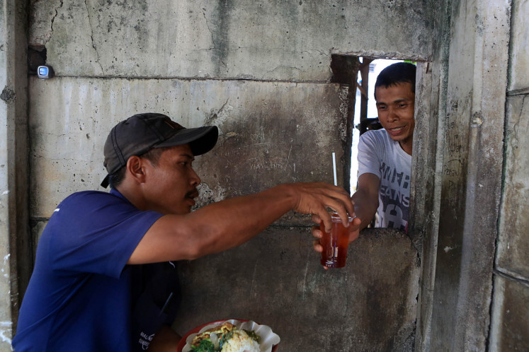 Hole in the wall: A customer buys food and a drink at a food stall in the Sudirman Central Business District (SCBD) in South Jakarta. Such stalls are popular among workers around the area as it sells food at a lower price than most restaurants in the area.