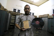 "Vintage and original: Lokananta production head Bemby Ananto shows an audiotape master and phonograph record of Indonesia's national anthem ""Indonesia Raya"" (Great Indonesia) recorded in 1959. JP/Maksum Nur Fauzan"