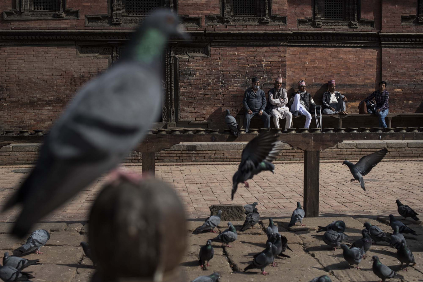 Locals love to spend their time sitting in Patan Square, where pigeons roam freely. JP/Rosa Panggabean