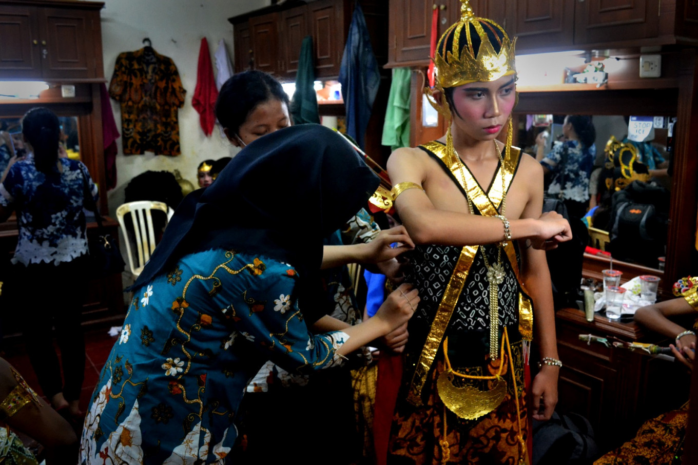 A student of SMPN 4 Surakarta junior high school is assisted with his 'wayang orang' costume backstage.