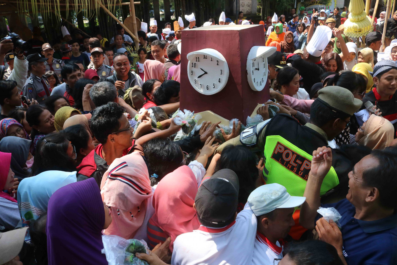 Crunch time: Residents scramble for 1.000 portions of jenang around a replica of Surakarta's clock monument. JP/Maksum Nur Fauzan