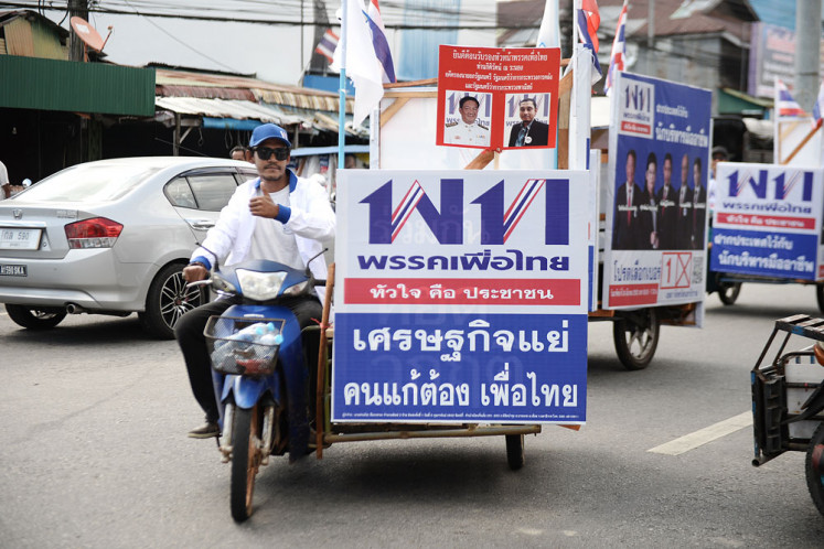 Supporters of a Phue Thai Party candidate campaign on motorbike in Thailand's southern province of Narathiwat on Thursday, ahead of the general election in March.