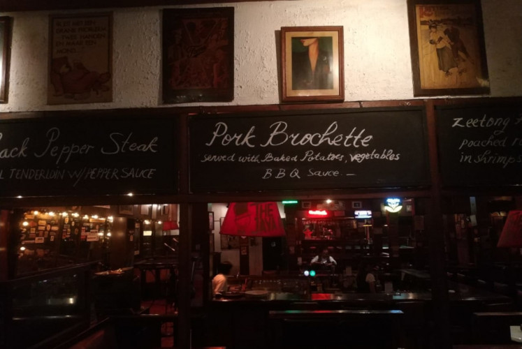Vintage posters and wooden furniture can be found inside The Jaya Pub, one of the legendary pubs of Jakarta.