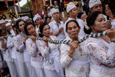 Balinese women hold up a long checkered fabric during Ngerebong. JP/Agung Parameswara