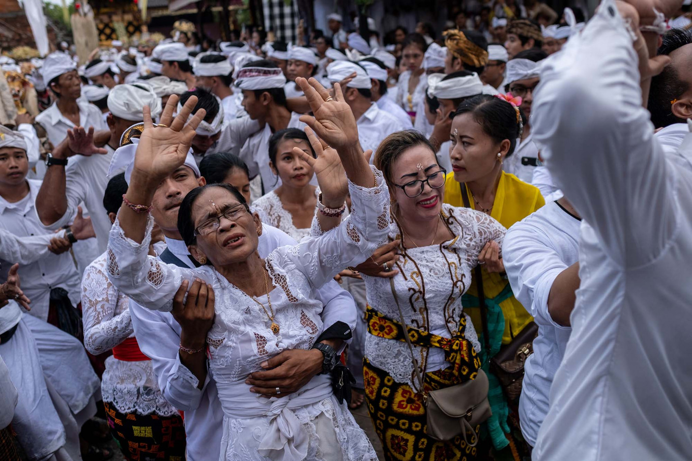 Balinese women become unconscious during the sacred ritual of Ngerebong at the Petilan temple on Jan. 13, in Denpasar, Bali. This ritual is said to achieve harmony between humans, nature and God. JP/Agung Parameswara