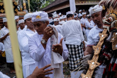 A Balinese man holds up Rangda, a sacred fabric, during Ngerebong. JP/Agung Parameswara