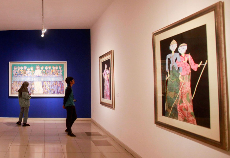 Wayang on canvas: Visitors look at Sasya Tranggono's works at the exhibition, which showcases her love for Indonesia and celebrates her 30-year career.