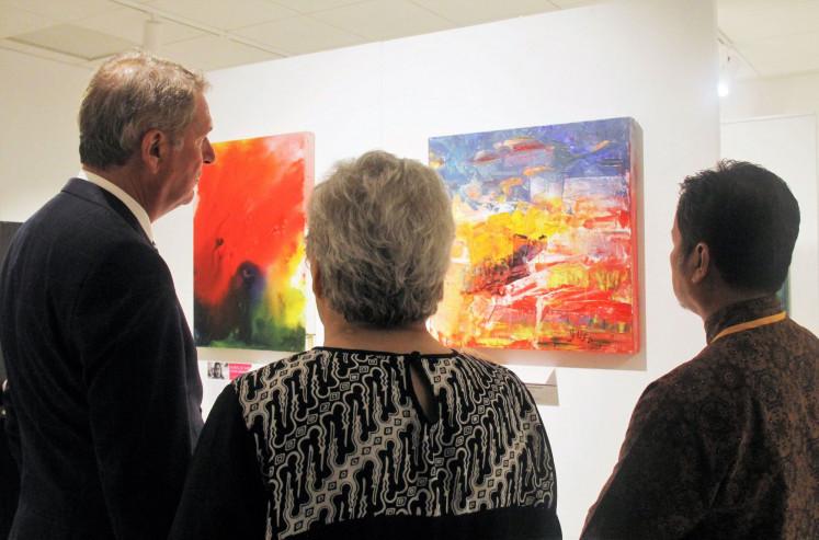 Color play: Dutch Ambassador for Indonesia Rob Swartbol (left) and art teacher Harry Bernadi (right) listen to Daya Pelita Kasih's co-founder Gitta S. van Engelen's explanation of the two displayed paintings.